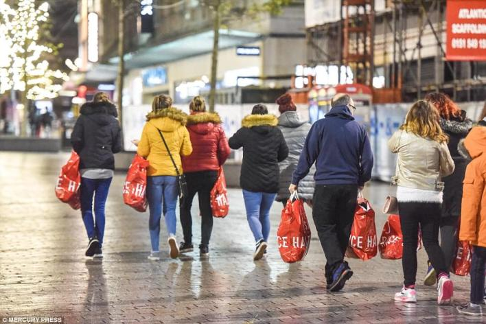 Millions of Brits are braving cold and miserable weather to find the best Boxing Day bargains on the high street this morning. Dedicated sales shoppers are pictured with their Next shopping bags in Liverpool city centre after stores opened at 6am