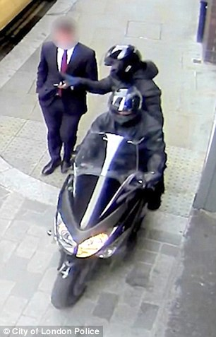 Threat: Moped muggers snatch a mobile phone from the hands of a City businessman