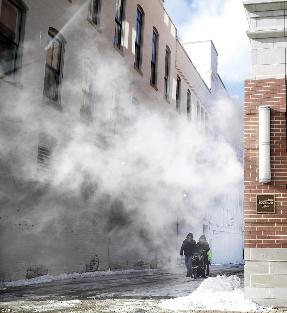 Pedestrians walk through steam from the Berkshire Bank building on North Street during a frigid winter day Wednesday in Pittsfield, Massachusetts