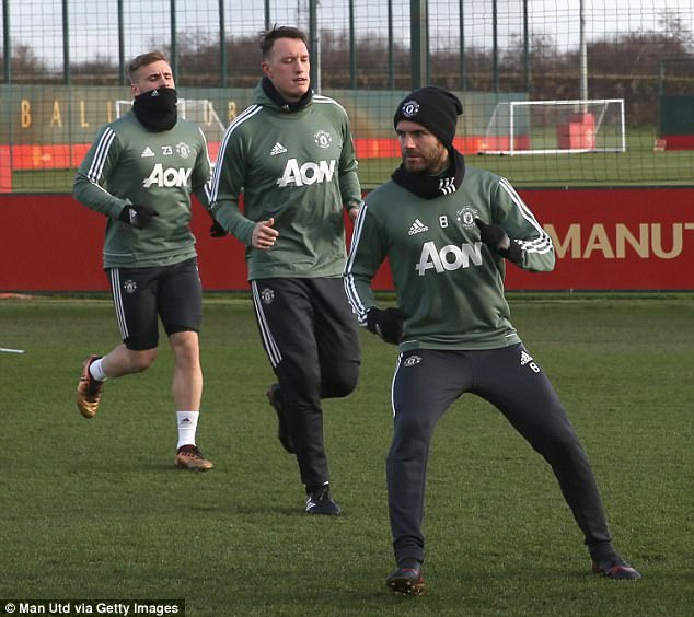 Luke Shaw (L) followed suit, while Juan Mata (R) wore a hat and Phil Jones (C) went without