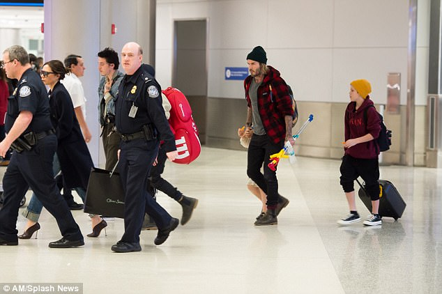 Making an entrance: The family were joined by two burly security guards as they strolled through the airport