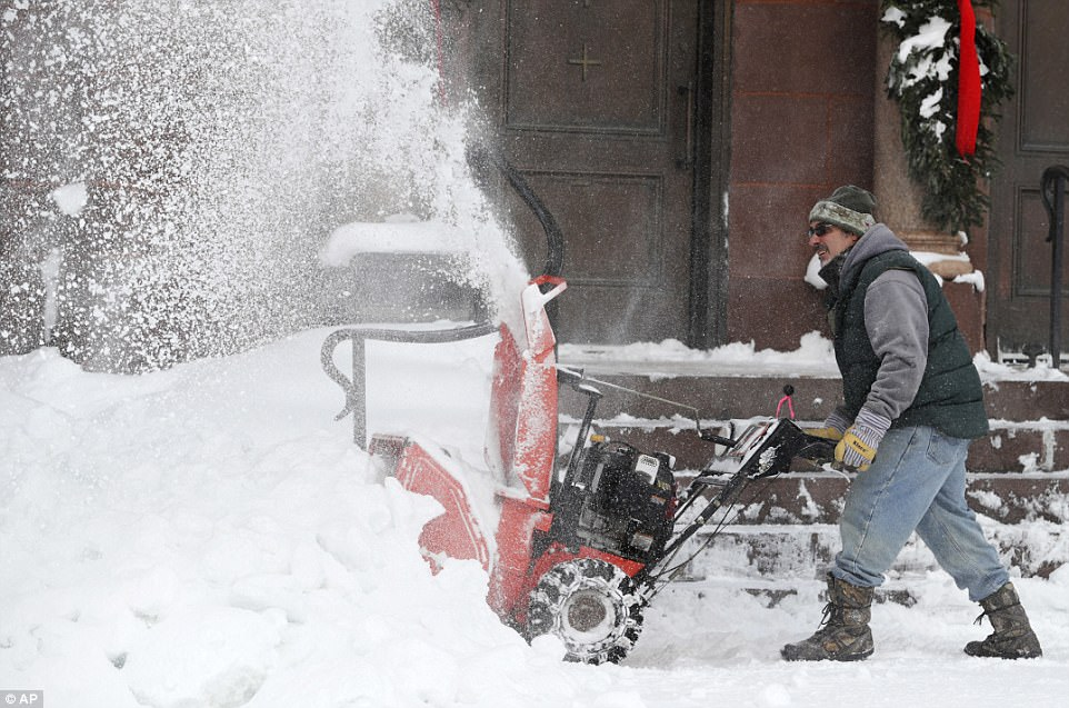 Frank Necci clears snow from St Andrews Catholic Church on Friday in Erie, Pennsylvania after a massive snow storm