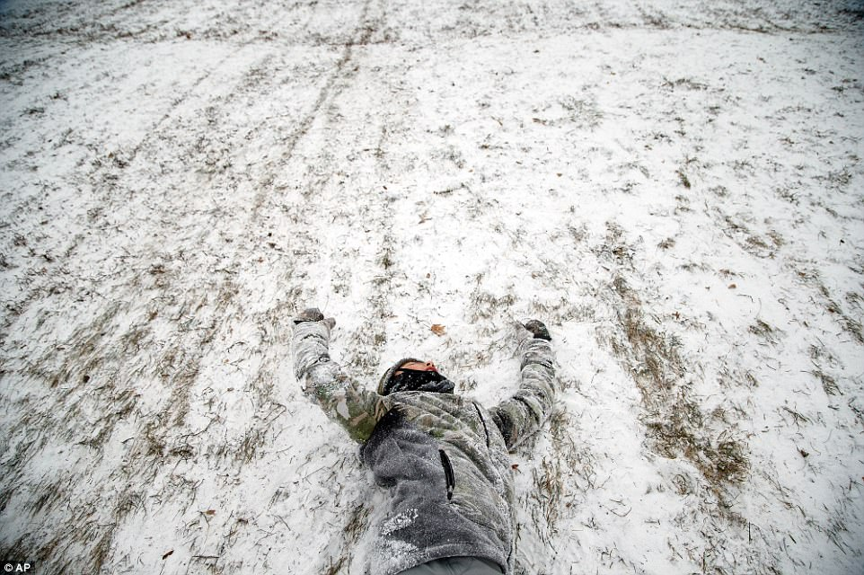 Frankie Lafuente, 11, lays in the snow after a crash with his brother while sledding down a hill on Friday in Des Moines, Iowa