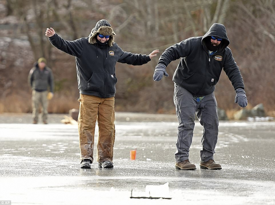 Jason Goldstein (left) and Jon Ross, slide across the ice to check the raised flag on an ice fishing tip up in Ledyard, Connecticut on Friday