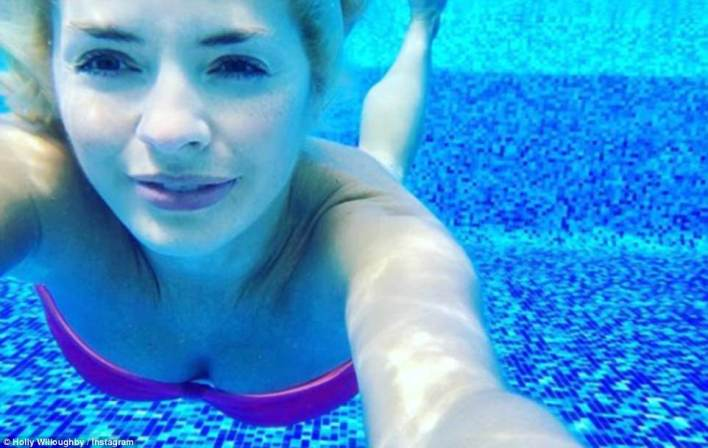 Sun-seeker:Holly revealed she had jetted overseas to see in 2018 on New Year's Eve, as she shared a cool underwater shot of her posing in the pool while clad in a colourful bandeau bikini