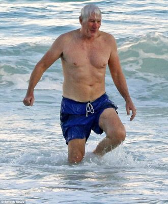 Fun in the sun: ShirtlessRichard Gere, 74, displayed his fit physique in a pair of blue board shorts as he enjoyed a relaxing New Year's Day at the beach in Tulum, Mexico, on Monday