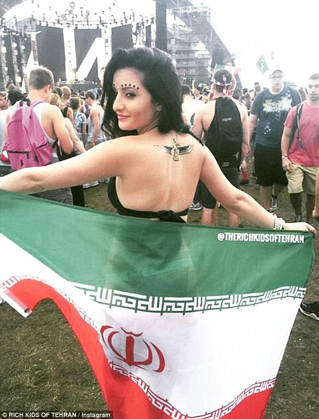 Loyalty: A woman poses with the Iranian flag at what appears to be a music festival abroad
