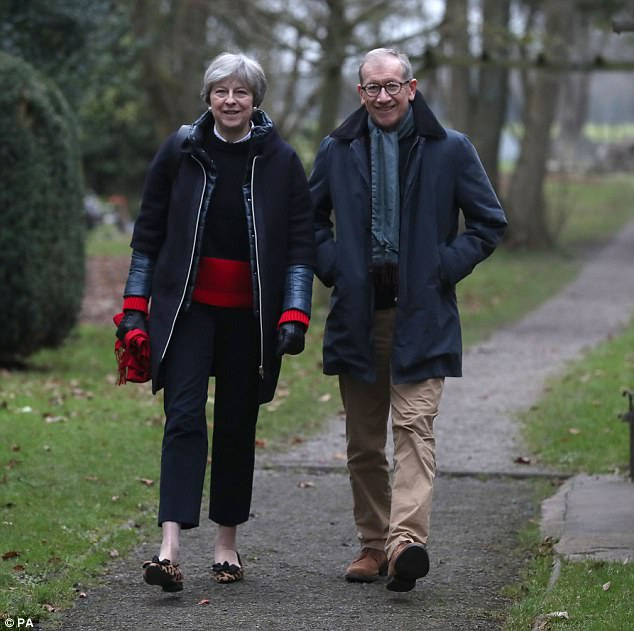 Theresa May (pictured at church in her Maidenhead constituency today with husband Philip) has insisted Mr Trump will come to the UK