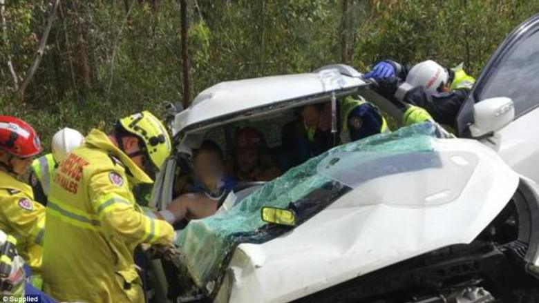Paramedics and NSW Fire and Rescue officers work to free Sam Lethbridge from his car after its discovery on Monday