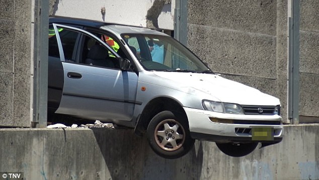 A woman has escaped without serious injury after her car smashed through a concrete railway barrier (pictured)