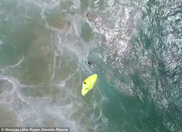 Footage shows the remote controlled aircraft fly above the teenagers before dropping an inflatable device