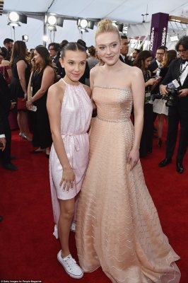 Having a blast! Stranger Things star Millie Bobby Brown (l), paired her blush halter Calvin Klein Pre-Spring 2018 dress with twin buns and Converse sneakers; posing with Dakota Fanning (r) who wore a Prada gown