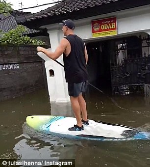 One man was seen putting his paddle boarding skills to good use as the water rose to chest height in some areas