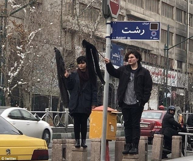 Two for one: Two young women are seen holding out their headscarves at an unknown location in Iran this week