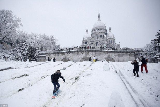 Aprovechar al máximo: un hombre disfruta del snowboard en la basílica del Sacre Coeur en Montmartre, después de que siete pulgadas de nieve cayeron sobre el norte de Francia y París durante la noche