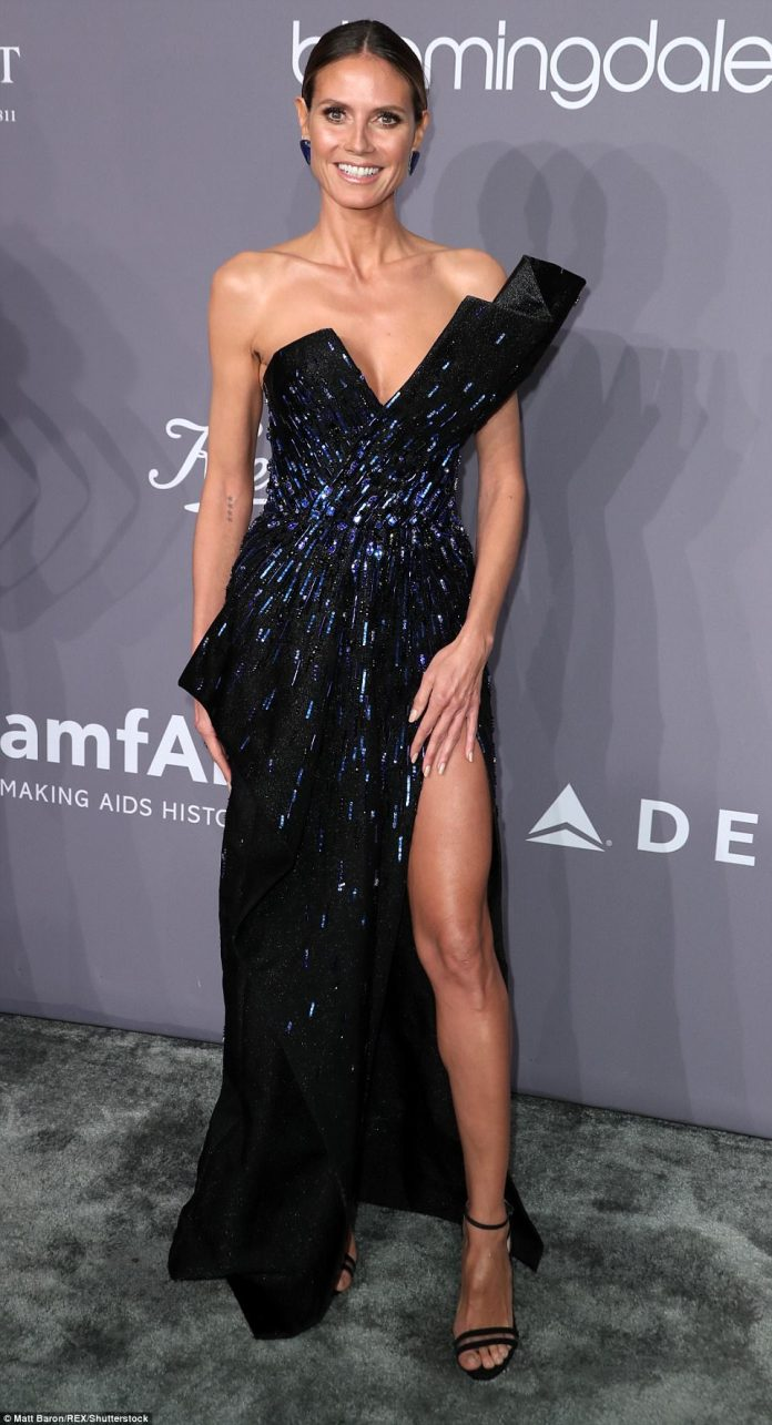 Heidi, 44, opted for a dramatic gown slit to the thigh and with a plunging neckline. She paired it with matching sandal heels and stunning earrings
