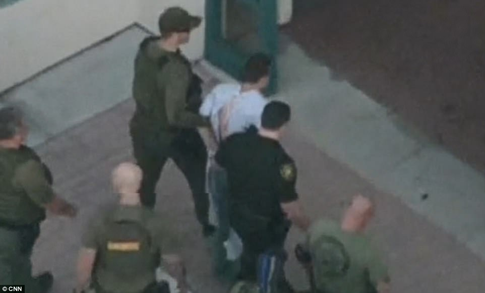 The suspected gunman was checked out at a hospital after his arrest (above in a hospital gown) and is now being held at a secure location in a public building