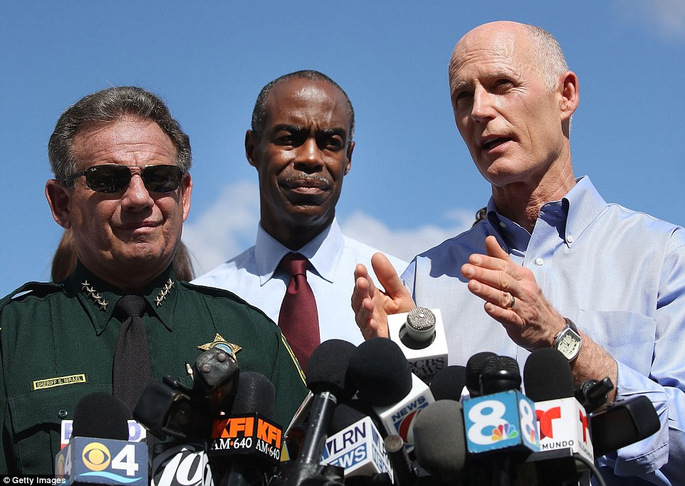 Florida Gov. Rick Scott, right, speaks to reporters at a Thursday morning press conference about the shooter