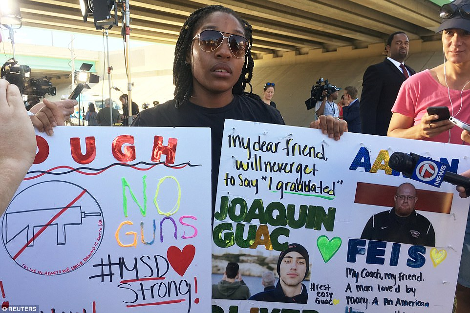 Tyra Hemans, a 19-year-old senior at Marjory Stoneman Douglas High School, sobs as she holds signs honoring slain teachers and friends near the police cordon around the school in Parkland Florida, U.S., February 15, 2018