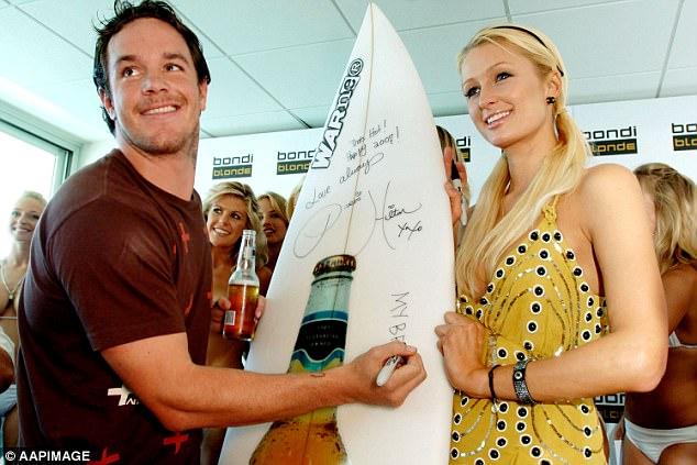 Original Bra Boy Koby Abberton signs a surfboard with heiress Paris Hilton at Bondi in 2007
