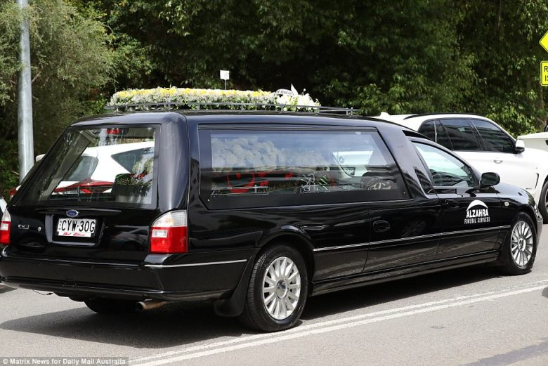 Both the hearse and Hawi's coffin were covered in a spray of flowers (pictured)