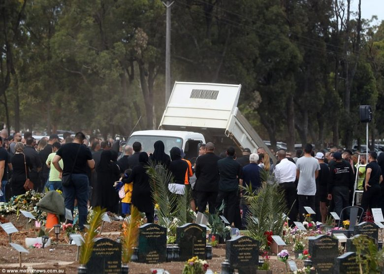 A truck is seen lowering something towards the grave site as mourners gather around
