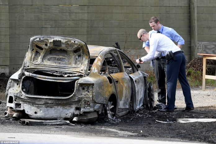 Police at the scene of a burnt out car in Robjant St, Hampton Park, near the scene of a shooting at a tattoo parlour in Melbourne.The men escaped in a silver saloon car before setting it on fire and are still on the run