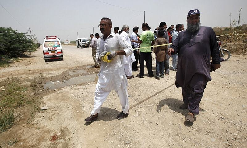 Security officials cordon off the area at the scene of an attack on a bus in Karachi, Pakistan, May 13, 2015. — Reuters