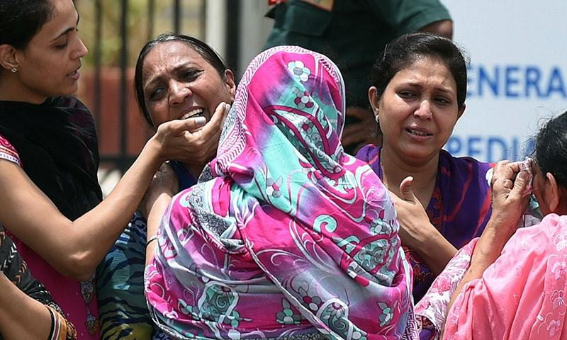 Ismailis mourn following an attack by gunmen on a bus carrying Ismailis outside a hospital in Karachi on May 13, 2015. —AFP