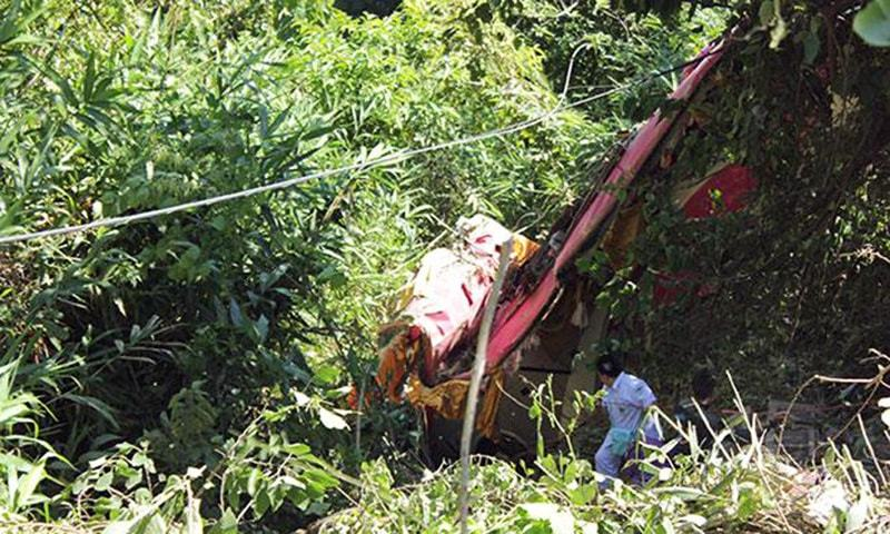 The wreckage of the tour bus in the ravine after it plunged off a winding hill road in Uttaradit's Muang district. ─Bangkok Post