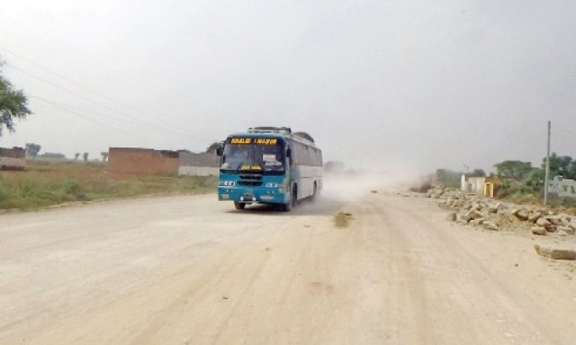 A passenger bus travels on the under-construction Chakwal-Sohawa Road. — Dawn