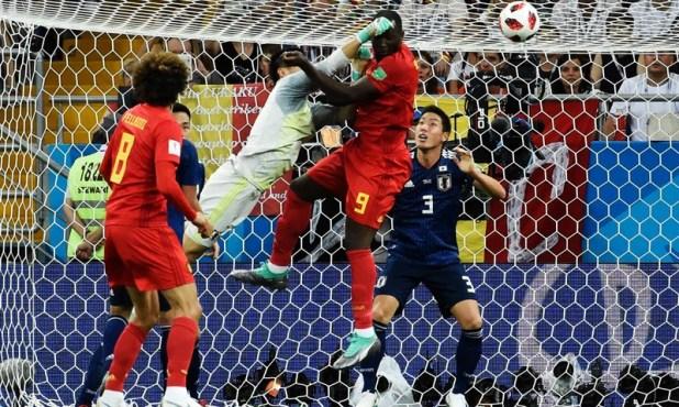 رومیلو لوکاکو جاپانی گول کیپر کے خلاف زور آزمائی کر رہے ہیں—تصویر اے ایف پی