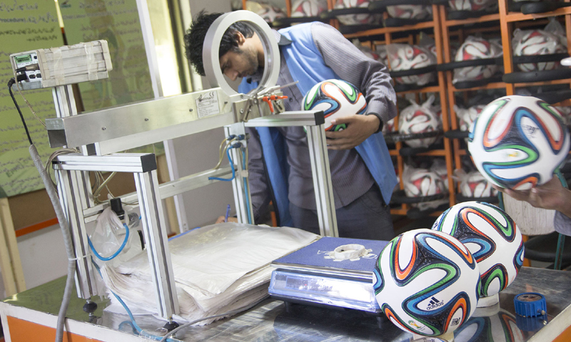 A worker puts the Brazuca through final tests after production