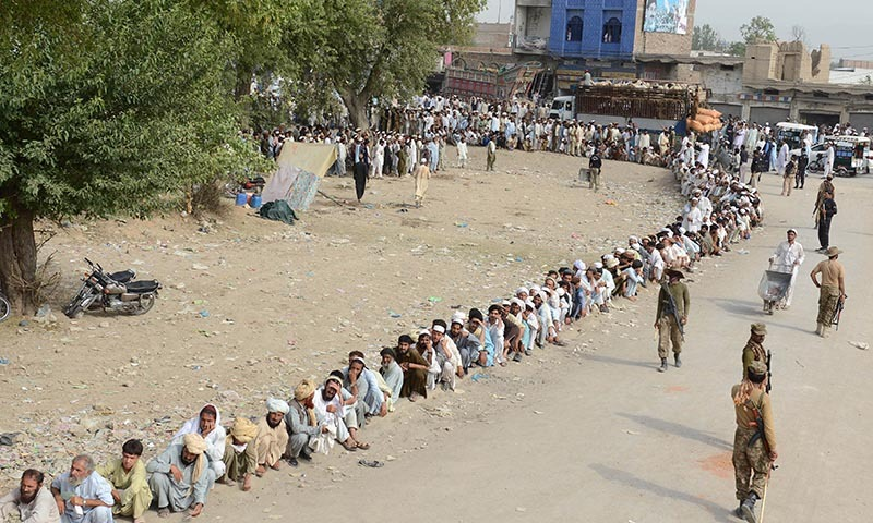 Internally displaced persons, fleeing  North Waziristan tribal agency, wait in line outside a World Food Programme aid distribution centre in Bannu on June 25, 2014.— Photo by AFP