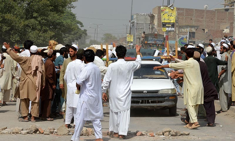 Internally displaced persons demonstrate against the delays in receiving food aid at a distribution centre in Bannu. — Photo by AFP