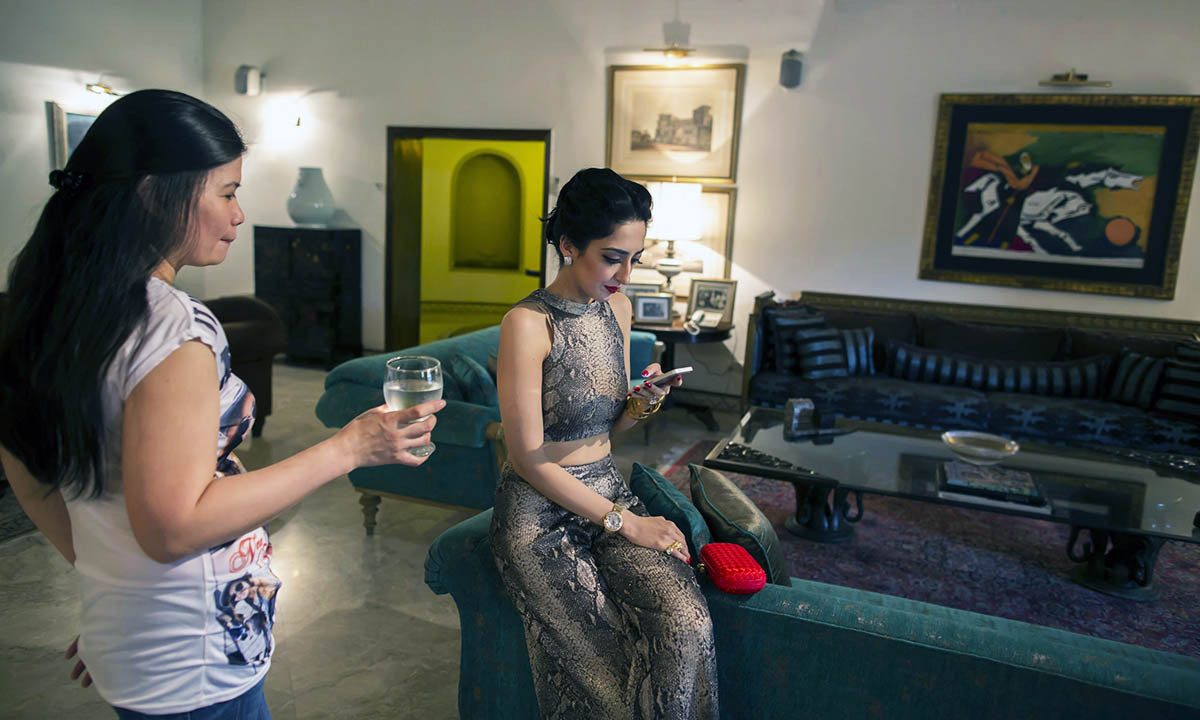 Educationalist and model Fatima (R) uses her mobile phone while her Filipino domestic worker holds her glass of water at her house in Lahore May 28, 2014.