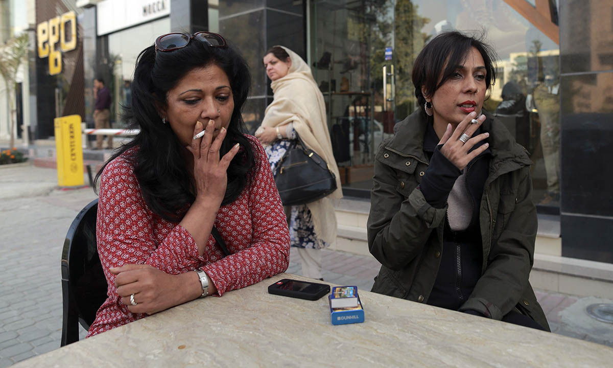 Pilates instructor Zainab Abbas (R) smokes a cigarette as she sits with a friend after lunch in Lahore February 19, 2014.