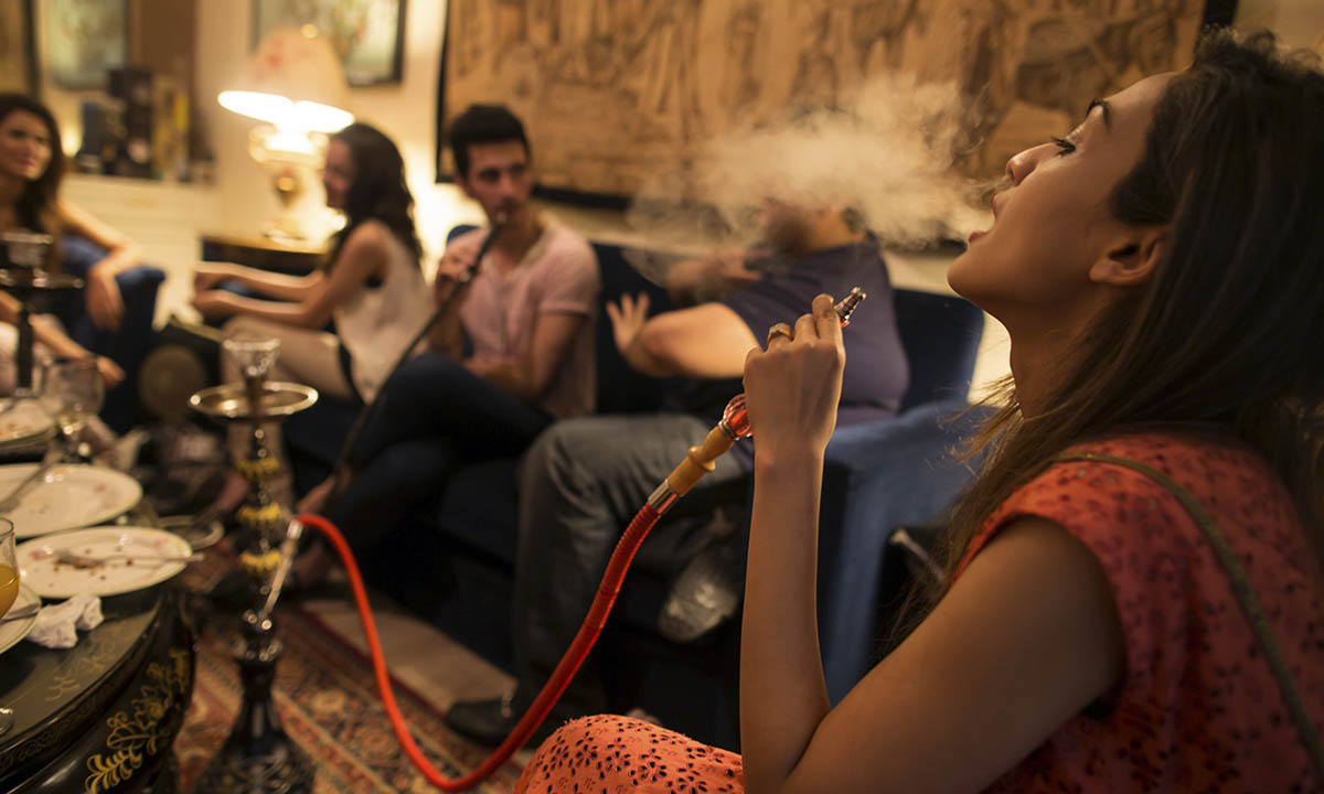 Sarah (R) and her brother, artist Usman Ahmed (2nd R), smoke a water pipe, also known as a narghile, as they sit with friends at home in Islamabad May 8, 2014.