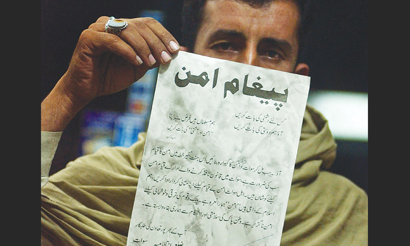 October, 2007: A citizen shows a leaflet dropped by the government from helicopters in Imamdehri, a village of Swat valley, urging them to support security forces in tracking down militants.—AFP file photo