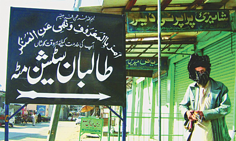 November, 2007: A militant stands outside the local police station in Matta, with a signboard announcing that it the station is now under control of the local Taliban.—AFP file photo