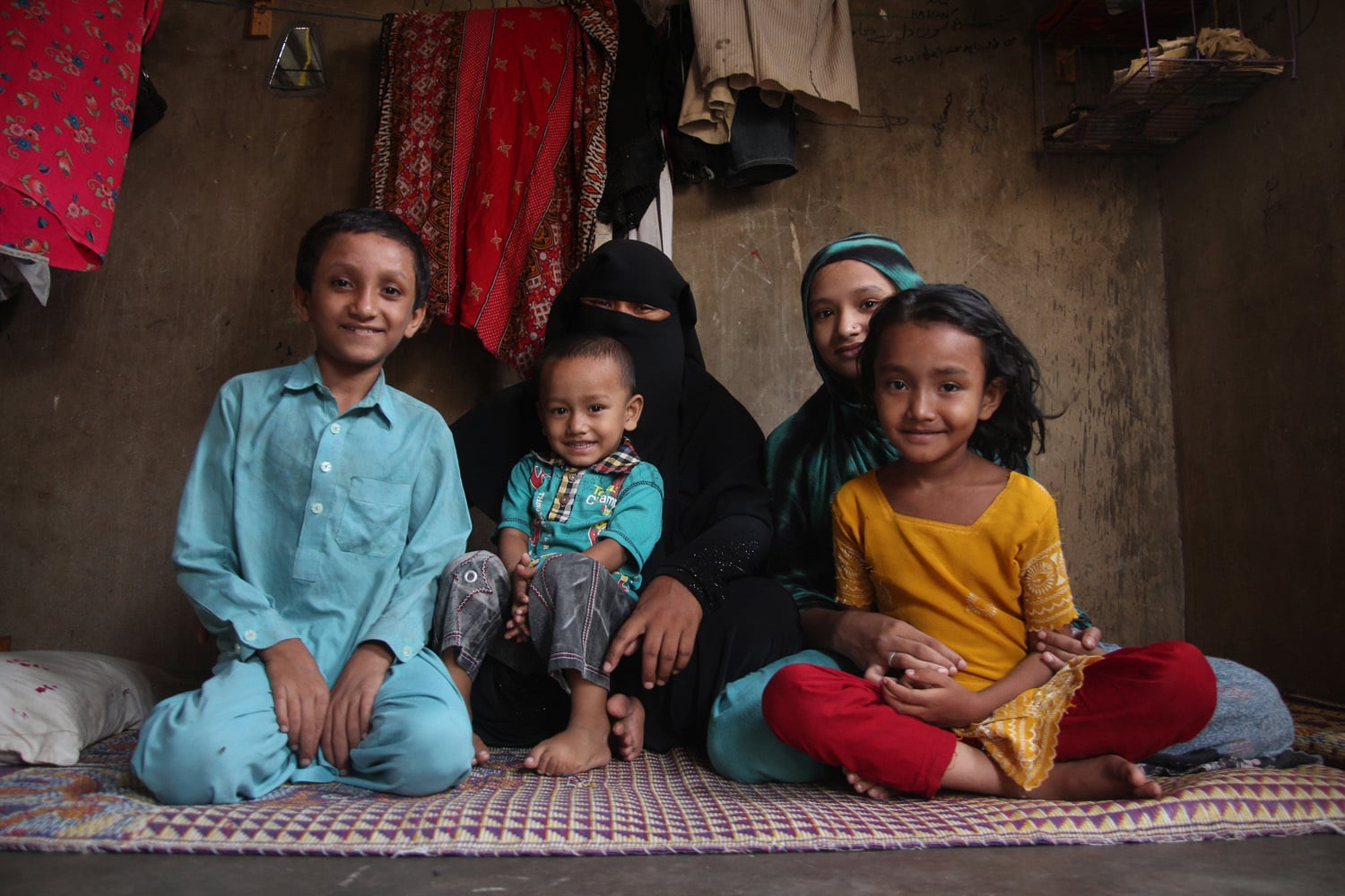 Anwara with her children in a single room quarter.