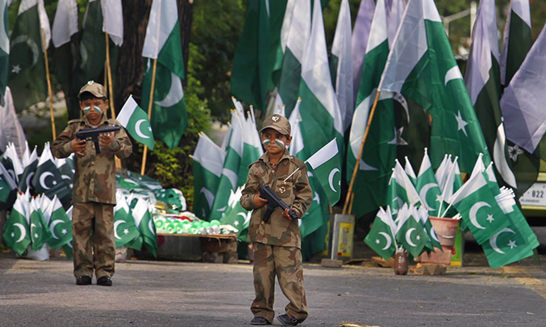 اسلام آباد میں جھنڈے فروخت کرنے والے ایک شخص کے بچوں نے پاکستانی فوجیوں کا روپ دھار رکھا ہے—۔فوٹو/ اے پی