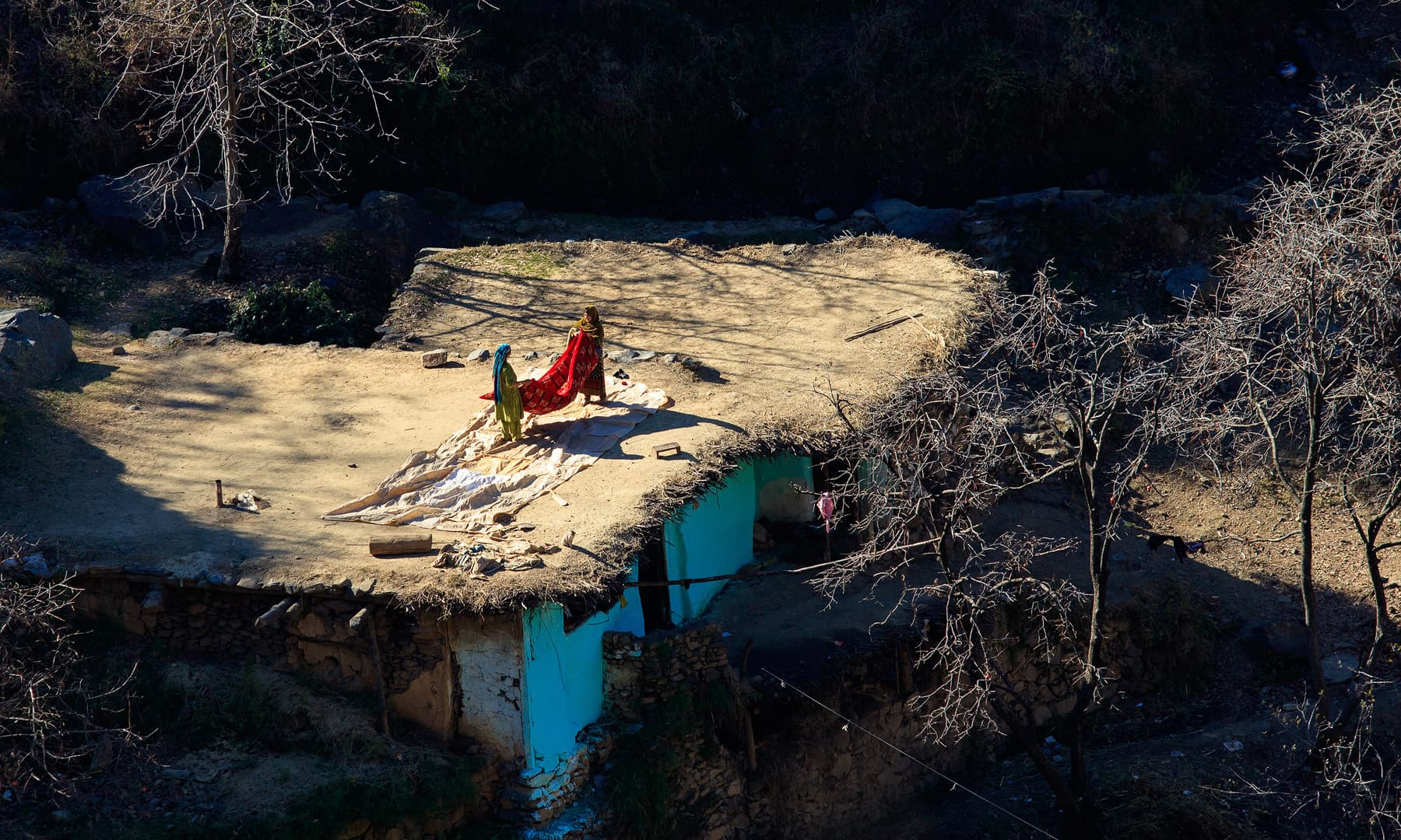 Girls working on the roof of their house.