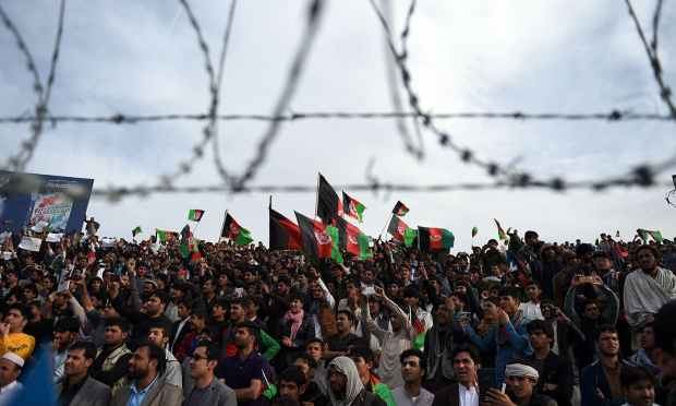 Afghan cricket fans cheer and wave the national flag. — AFP
