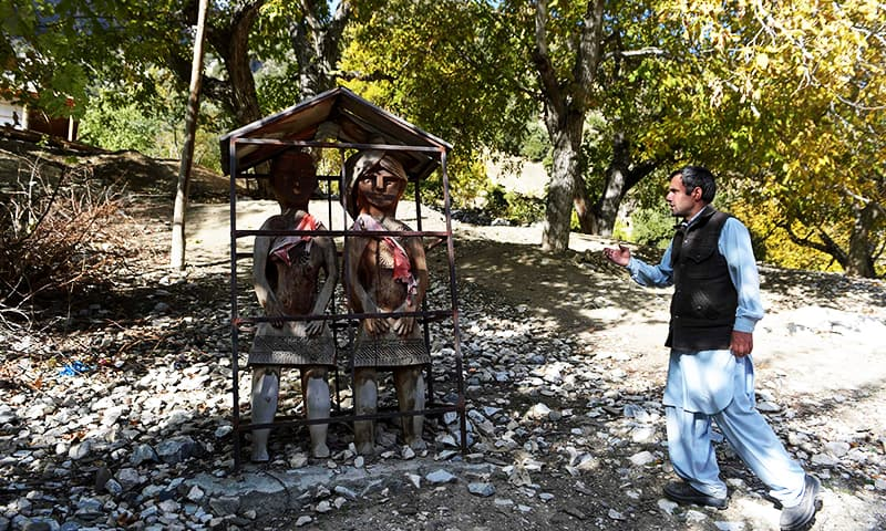 Kalash Peoples Development Newtwork (KPDN) activist Luke Rehmat stands near an altar during an interview with AFP in Brun village in the Bumboret valley. — AFP