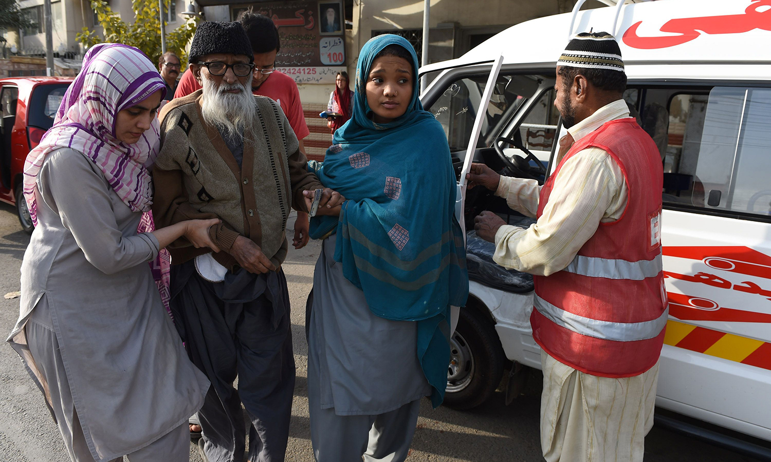 Abdul Sattar Edhi(2nd L) is assisted by staff as he arrives at his office in Karachi.  – AFP