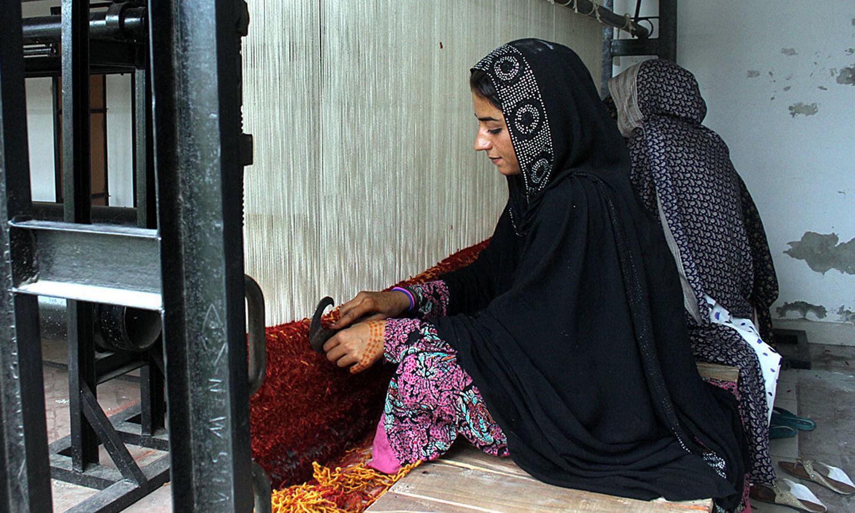 لاہور میں خاتون ورکرز قالین  تیار کررہی ہیں — اے پی پی فوٹو