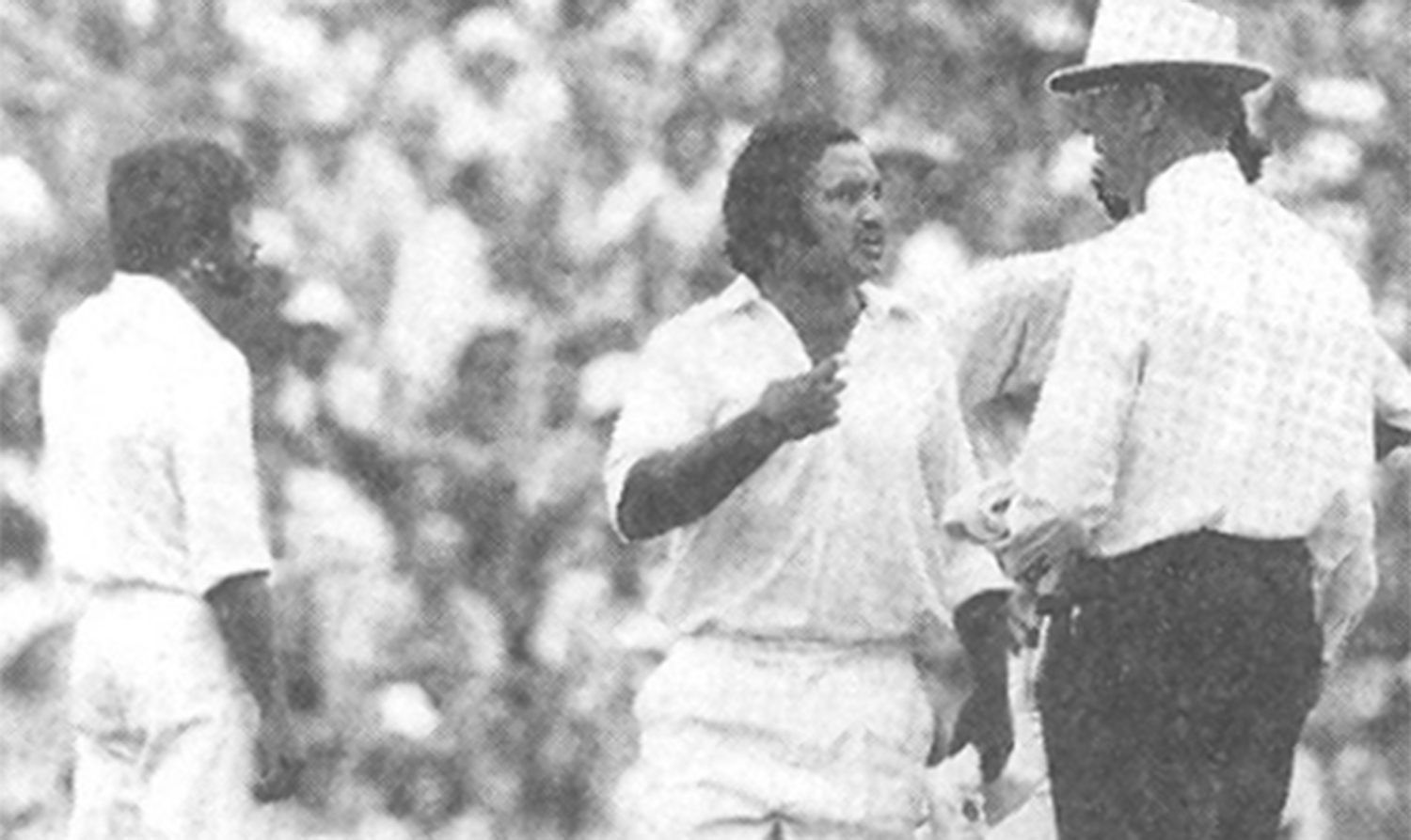 Mushtaq argues with the umpire. Imran is standing behind the umpire with hands on his hips. Also seen in the picture is substitute fielder, Wasim Raja.