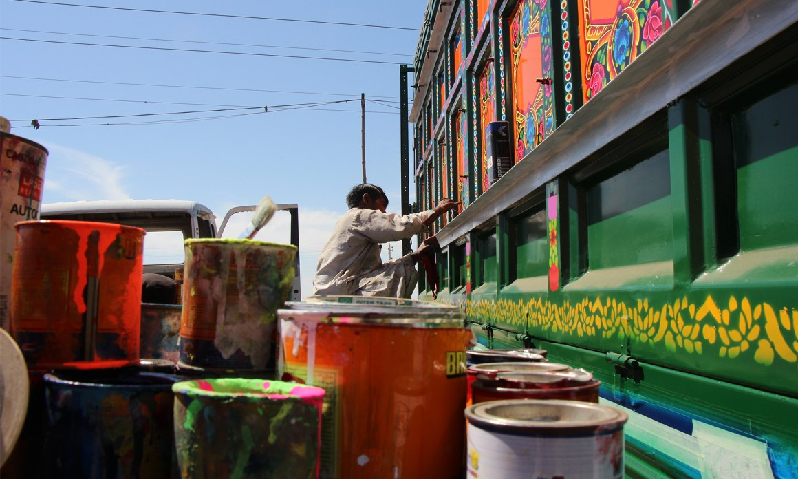 A young boy paints the body of the truck in Karachi