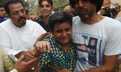 Relatives comfort Mujjudid Sabri (C), Amjad Sabri's son.